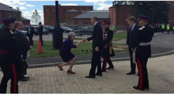 Elected British PM Theresa May genuflects to the heir to the throne